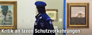 Polizist betrachtet von außen die Museumsräume