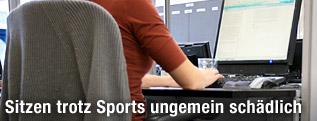 Person sitzt vor Computerbildschirm