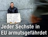 Ein Mann sitzt mit einem Schild auf der Straße und bittet um Geld