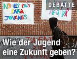 """Junger Mann mit Kapuzenpullover geht an einem Schild mit der spanischen Aufschrift """"No es pais para jovenes"""" (""""Jugend ohne Zukunft"""") vorbei"""