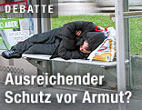 Mann liegt bei einer Straßenbahnhaltestelle auf der Wartebank und schläft