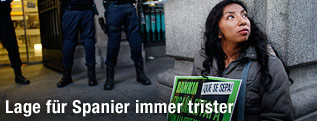 Frau sitzt mit einem Schild auf der Straße
