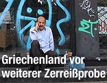 Ein Mann sitzt vor einem mit Graffiti bemalten, geschlossenen Geschäft