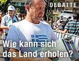 Mann hat auf seinem T-Shirt eine griechische Flagge und trägt eine Kartonschachtel