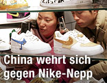 Chinesische Teenager sehen sich Nike-Sneaker in einem Glasregal an