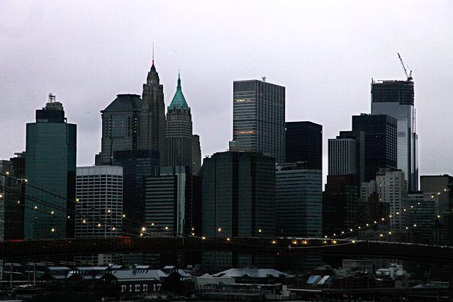 Die beleuchtete Brooklyn Bridge mit der nach dem Stromausfall dunklen Skyline von Manhattan im Hintergrund