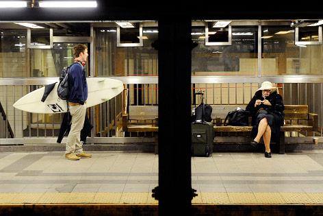 Mann mit Surfbrett wartet auf eine U-Bahn