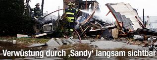 Feuerwehrmann löscht eingestürztes Haus in  Lindenhurst, N.Y.