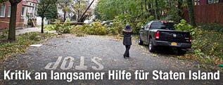 Frau steht auf einer Straße vor einem umgestürzten Baum