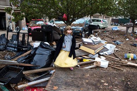 Ein kleines Mädchen steht in einem Haufen angeschwemmter Trümmer