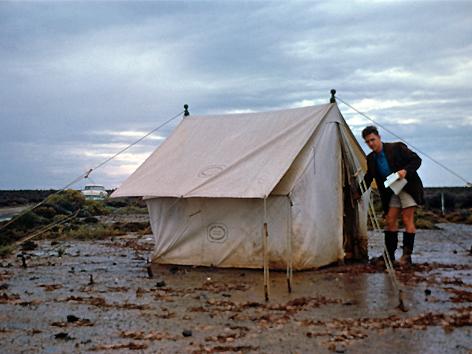 Wissenschaftler vor Zelt bei verregneter Standortsuche in Südafrika