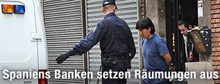 Ein Mann wird von spanischer Polizei nach einer Zwangsräumung aus dem Haus geführt