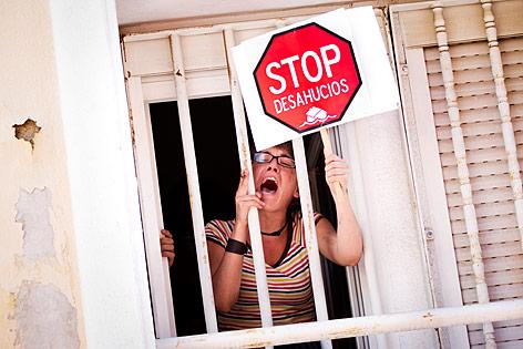 Eine Frau protestiert mit einem Schild und lautem Schreien gegen eine Zwangsräumung