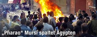 Mursi-Gegner stehen vor dem brennenden Parteibüro der Muslimbrüderschaft