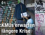 Ein Einzelhändler hängt Kleidung vor sein mit Graffiti beschmiertes Geschäft