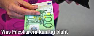 Person hält einen Hundert-Euro-Schein in der Hand