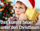 Ein Bub mit Weihnachtsmannmütze horcht an einem verpackten Geschenk