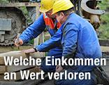Arbeiter mit Helm schlagen einen Nagel ein