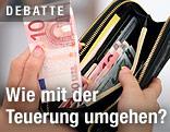 Eine Hand nimmt zehn Euro aus einer Geldbörse