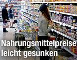 Frau steht in einem Supermarkt vor einem Regal