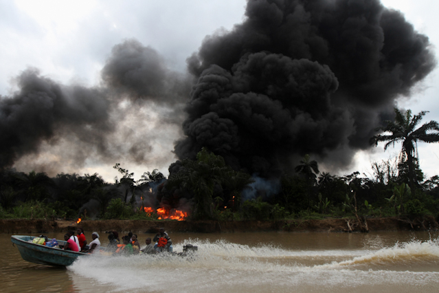 Boot vor brennender Raffinerie