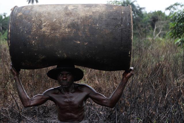 Mann trägt Ölfass