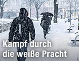 Personen gehen im Schneefall auf schneebedecktem Gehsteig