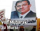 Demonstrant hält Plakat mit Bild von Mursi und Mubarak in die Höhe