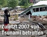 Ein Mann steht vor den Trümmern seines Hauses