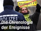 """Eine Demontrantin hält ein Schild mit durchgstrichenem """"Stuttgart 21""""-Schriftzug und steht vor einem Polizisten"""