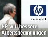 Frau geht an dem Firmenlogo von Hewlett Packard vorbei