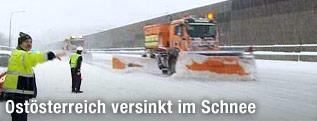 Polizist und Schneeräumfahrzeug auf der Autobahn