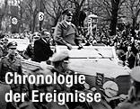 Adolf Hitler fährt in einem Auto umgeben von einer Menschenmenge durch Wien