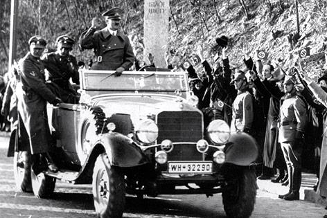 Adolf Hitler in einem Auto an der Stadteinfahrt von Wien umgeben von jubelnden Anhängern