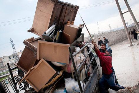 Flüchtlinge beladen einen Kleinlaster mit Möbeln