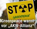 Hand hält ein Greenpeace-Schild
