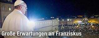 Papst Franziskus blickt von dem Balkon aus auf die Menschenmasse an Gläubigen auf dem Petersplatz