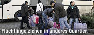 Flüchtlinge beladen einen Bus für den Umzug ins neue Quartier