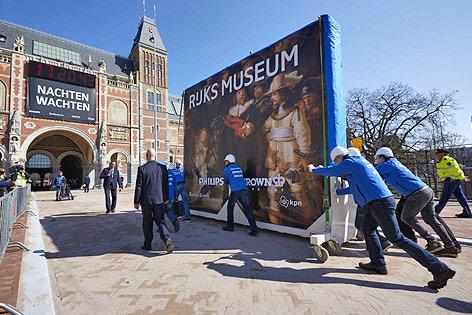 """Arbeiter transportieren das verpackte Gemälde """"Die Nachtwache"""" von Rembrandt von Rijn in das Amsterdamer Reichsmuseum"""