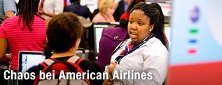 Angestellte der American Airlines spricht mit Passagieren