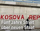 """Mann vor einer Wand mit der Aufschrift """"Kosova Republike!"""""""