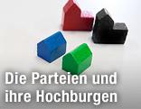 Sujetdarstellung der Parteien SPÖ, ÖVP, FPÖ und Grüne mit farbigen Holzbausteinen