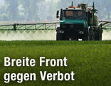 Traktor versprüht auf einem Feld Pestizid