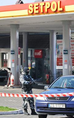 Mann mit einem Maschinengewehr bei der Setpol Tankstelle