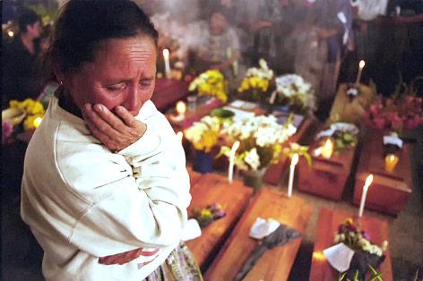Frau weint vor zahlreichen Särgen