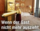Geöffnete Tür mit Schlüssel führt zu einem Hotelzimmer