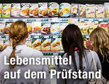 Mädchen stehen vor einem Kühlregal voller Lebensmittelprodukte
