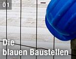 Zaun vor eine Baustelle mit blauem Schutzhelm