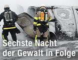 Feuerwehrmänner löschen brennende Fahrzeuge