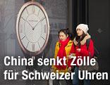 Frauen gehen an einer Reklame für Schweizer Uhr vorbei